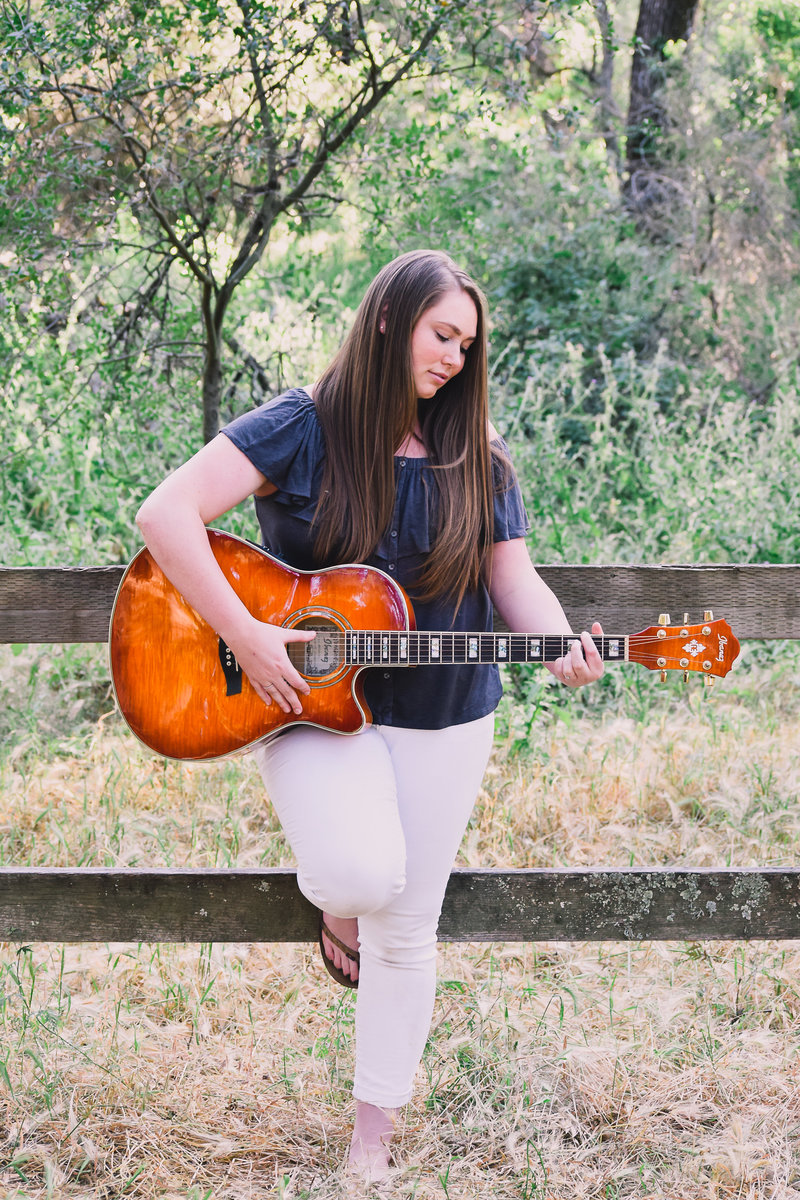 senior portrait - high school senior girl playing her guitar in the park