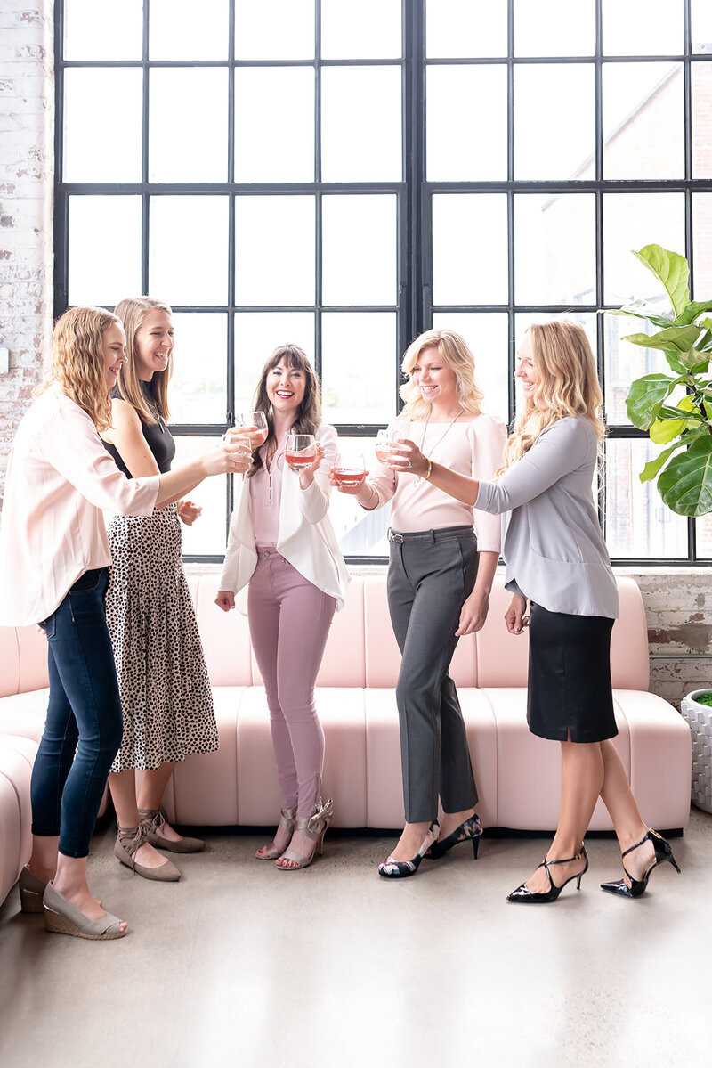 group of women toast with cocktails