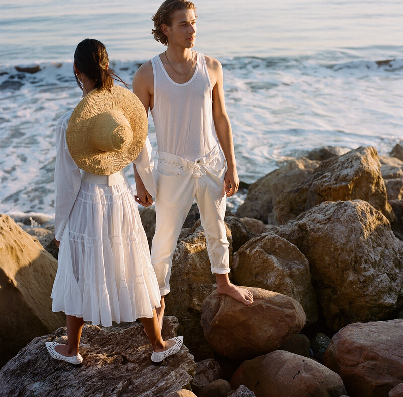 Man and woman in white stand on beach side rocks