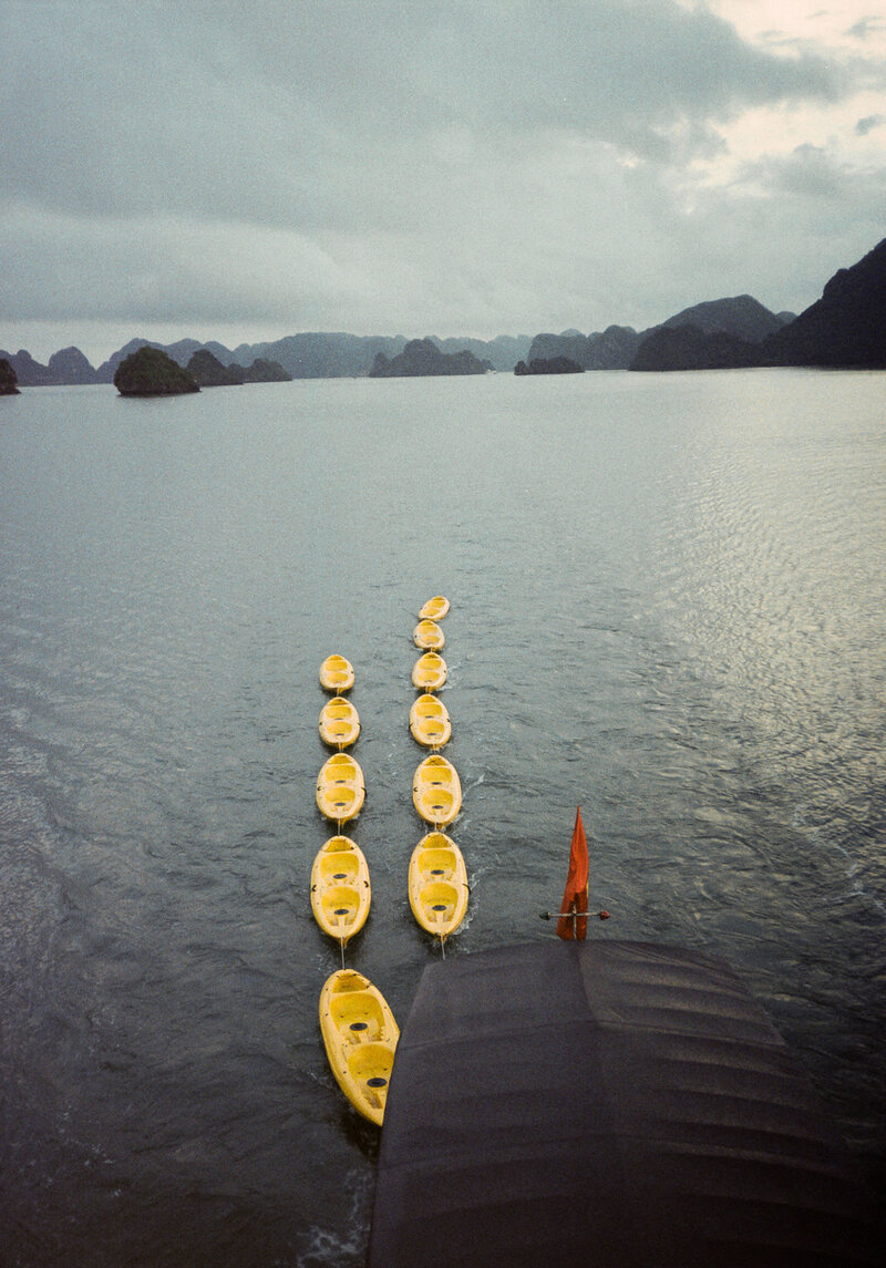 Yellow kayaks trailing a cruise boat on Ha Long Bay