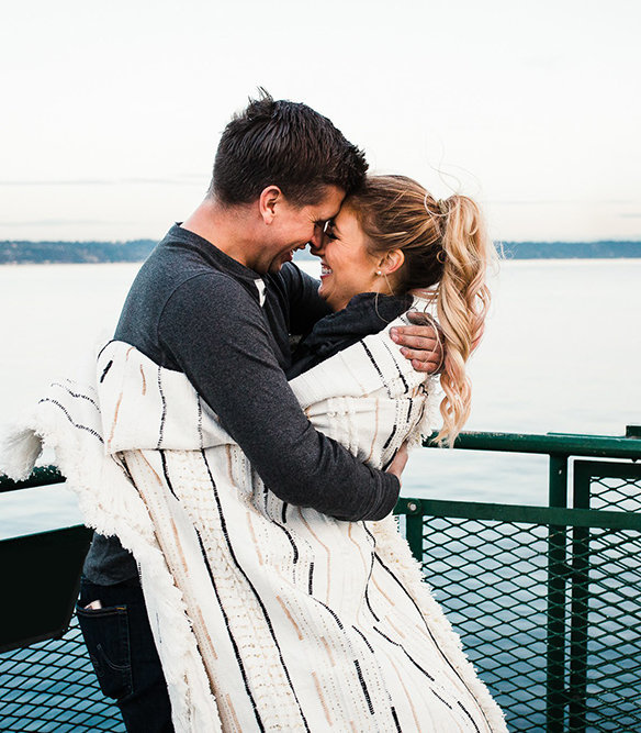 a couple snuggles under a blanket as they ride the ferry across puget sound and enjoy views of mt rainier in the background during their adventure engagement session with amy galbraith