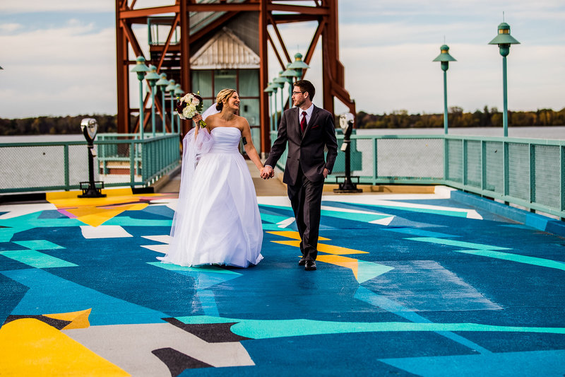 Bride and groom walking across the mural at the Bicentennial Tower in Erie, PA