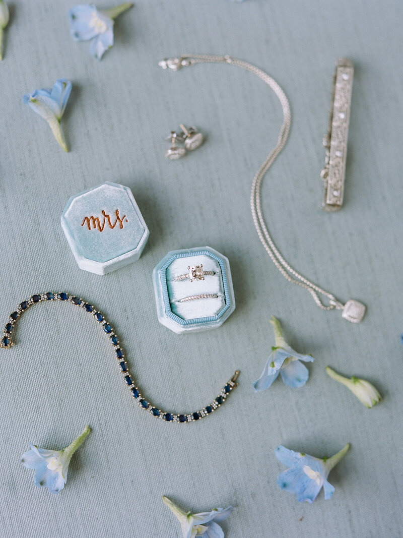 "Wedding accessories scattered with small blue flowers, a silver and sapphire bracelet, wedding rings in blue box marked with ""Mrs."", silver necklace and matching earrings"