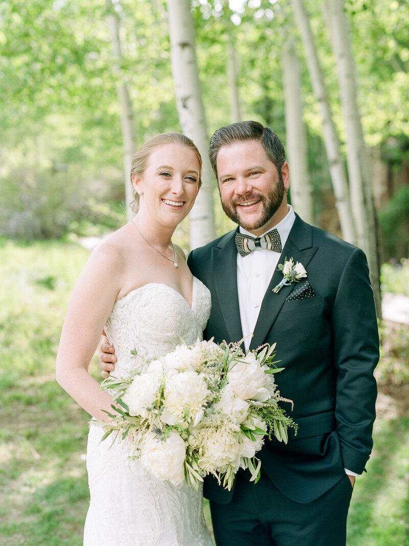 Testimonial photo of bride and groom holding large white bouquet, trees behind