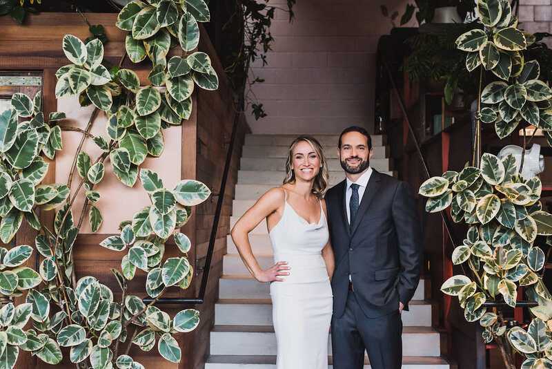 Bride and groom stand at the base of a staircase covered in greenery on their wedding day