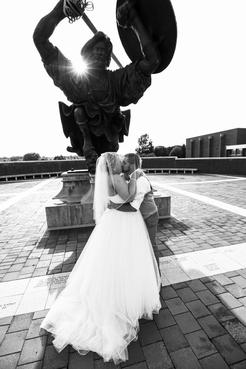 bride and groom kiss under fighting scot statute on the campus of Edinboro University