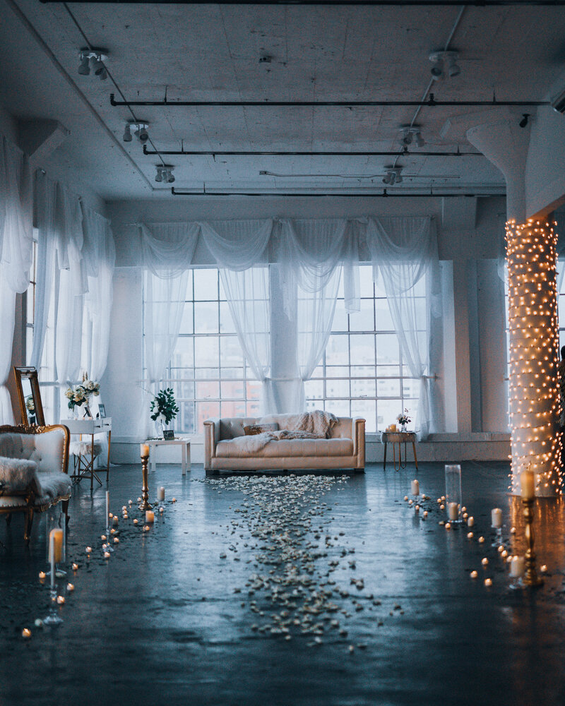 A warehouse loft apartment is set for a wedding proposal with rose petals, candles and fairy lights.