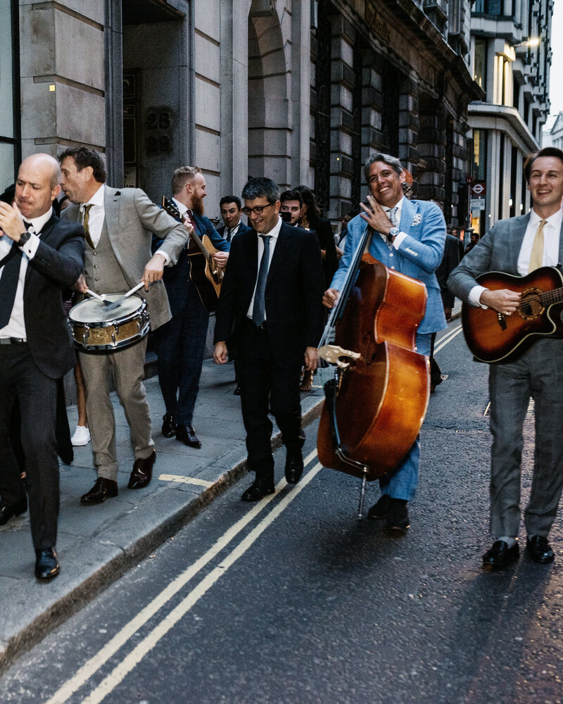 A roaming band play their instruments alongside wedding guests in the street at a party in London.