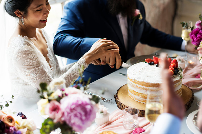 Canva - Couple Hands Cutting Wedding Cake