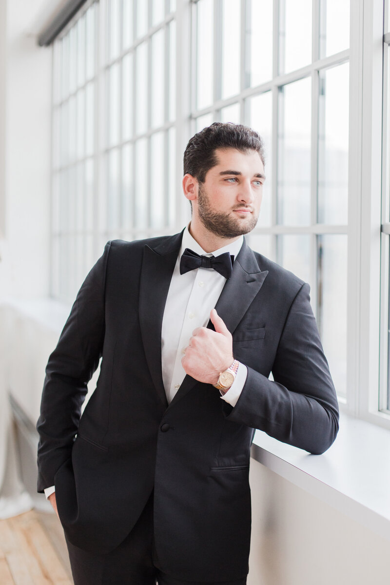 groom standing beside window in tux on wedding day by costola photography