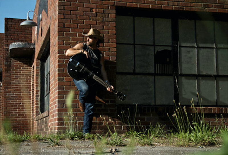 Country Music Photo Musician Billy Lord standing against brick building leaning on guitar he holds