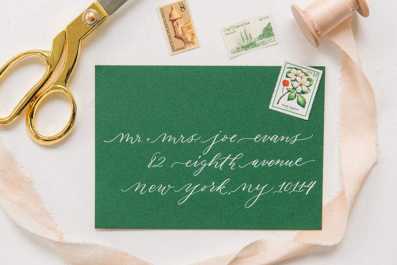 Airy and romantic white ink calligraphy on a green wedding envelope by Lewes Lettering Co