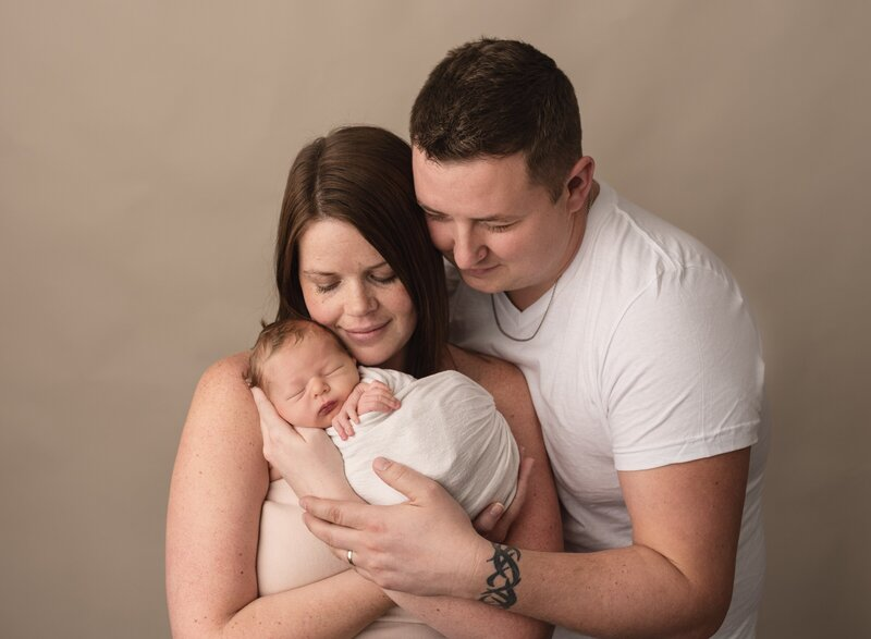 mom and dad holding a newborn in aphotography studio in saint john
