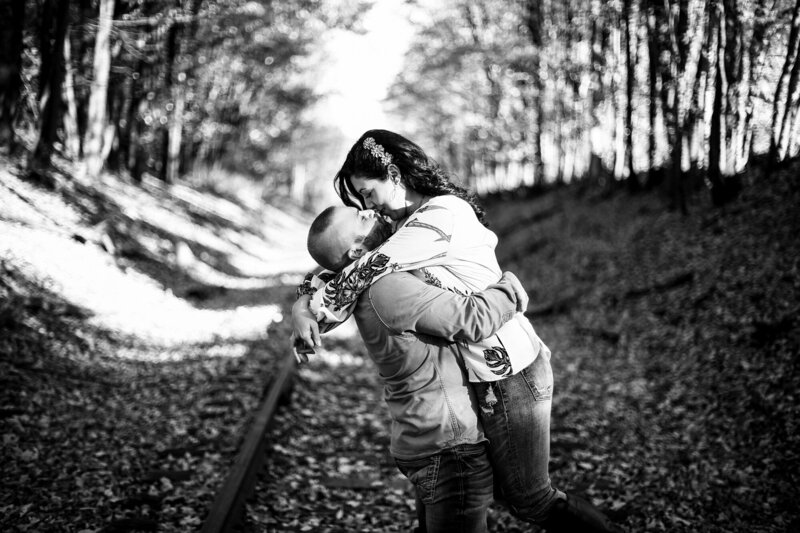 Man lifts and kisses woman on abandoned train tracks for engagement photos in Edinboro PA