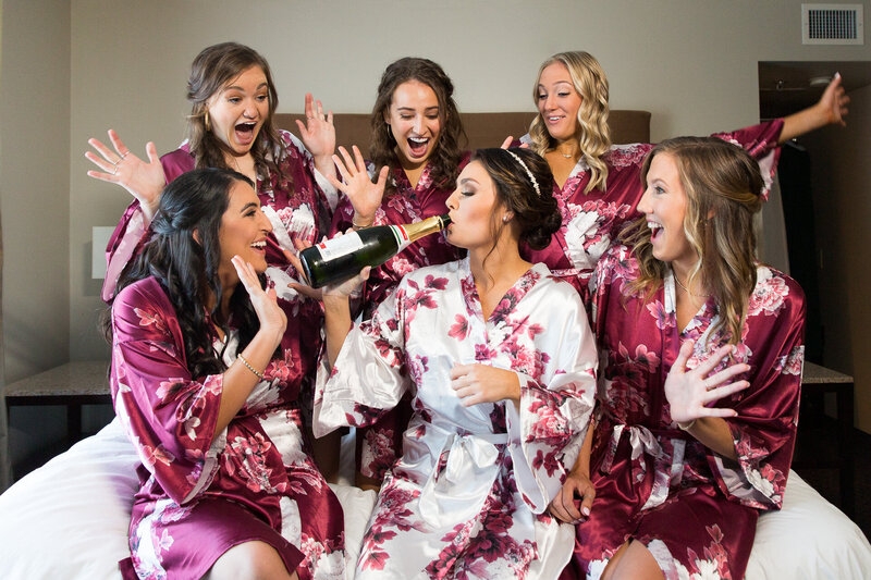 bride and bridesmaids drinking champagne in robes on hotel bed on wedding day