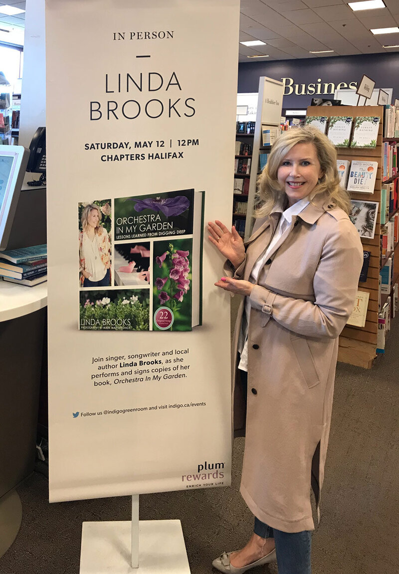 Marketing materials image Author Linda Brooks beside Chapters in store display Book Signing Orchestra In My Garden