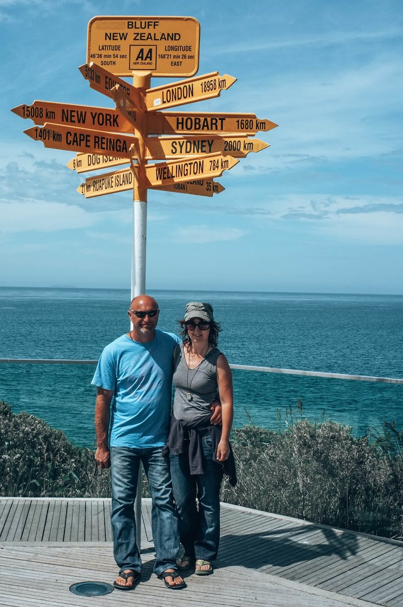 Lynda and Warren standing in front of iconic sitrling point signpost at Bluff, New Zealand