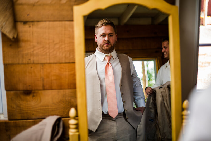 Groom looks in mirror while getting ready at Port Farms