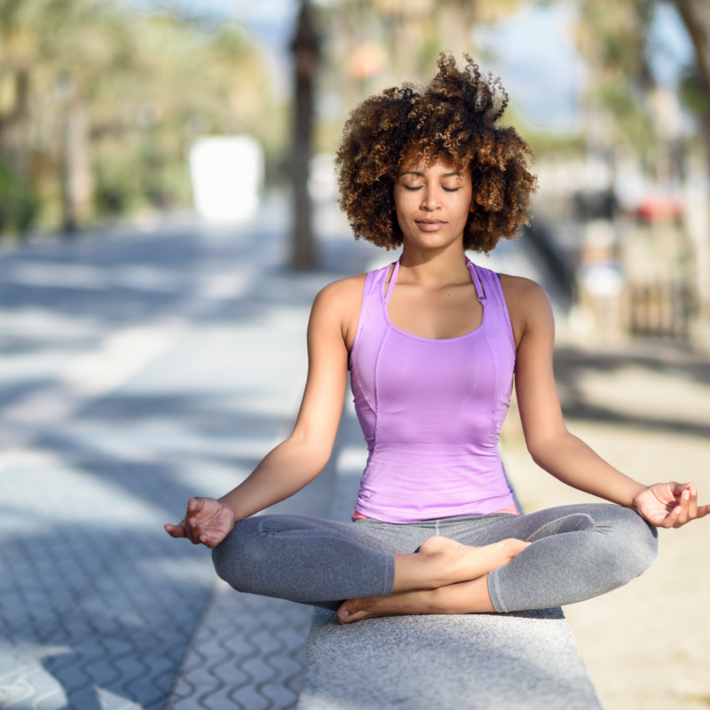 A woman smiling as she meditates on the sidewalk wearing a purple tank top & yoga pants
