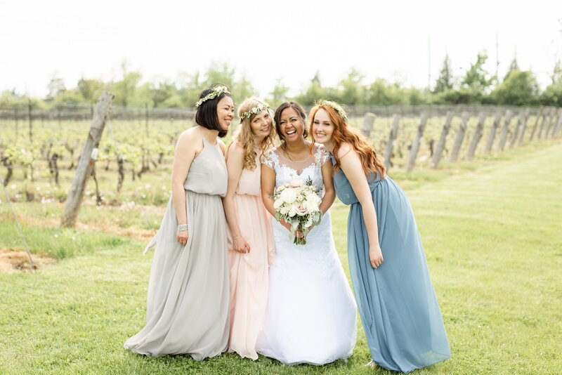 Bridesmaids surround the bride as they laugh together at Cave Springs Winery