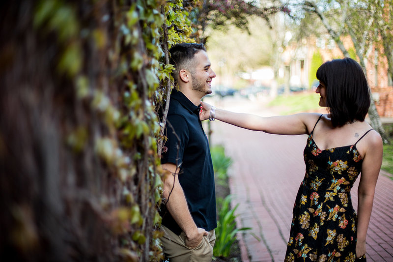 Woman playfully grabs man's shirt collar in spring engagement photos at Modern Tool Square