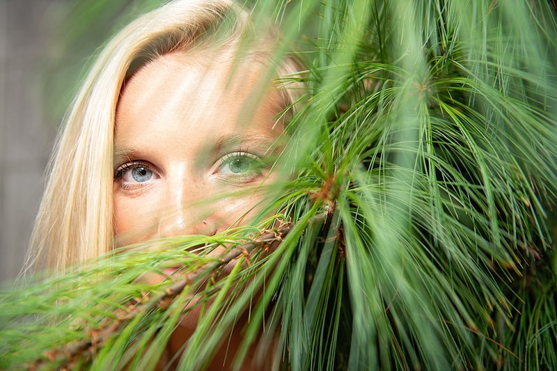 High school senior girl peeking out from behind green  pine branches