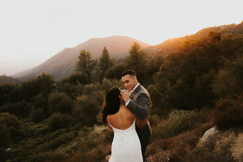 bride and groom embracing in front of mountains