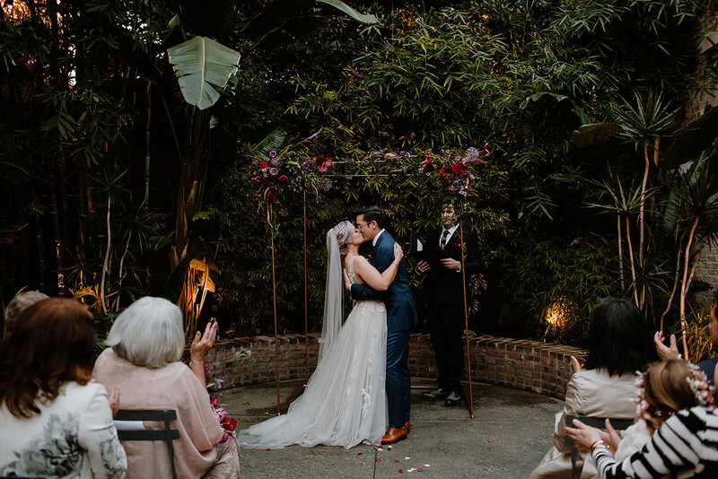 Bride and groom take their first kiss as a married couple in jungle like courtyard ceremony