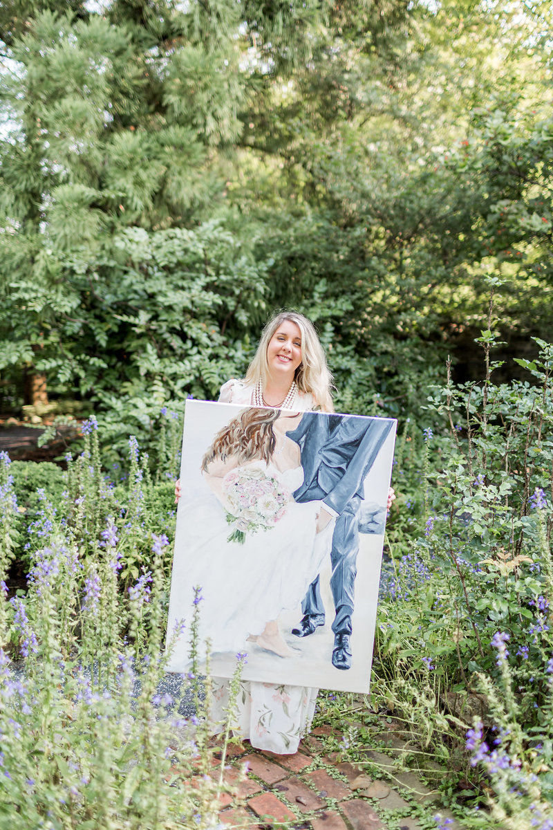 Live painter Brittany Branson shows the bride and groom their painting at Keswick Vineyards in Charlottesville Virginia