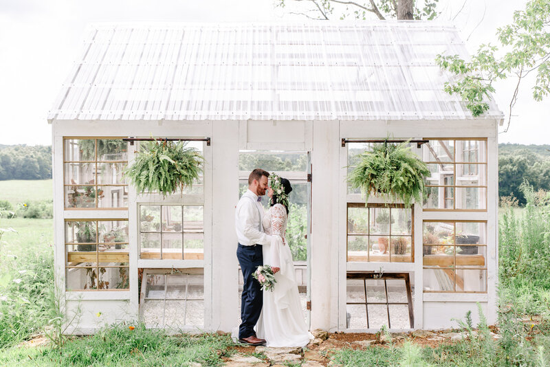 A bride and groom pose in front of a white rustic greenhouse.