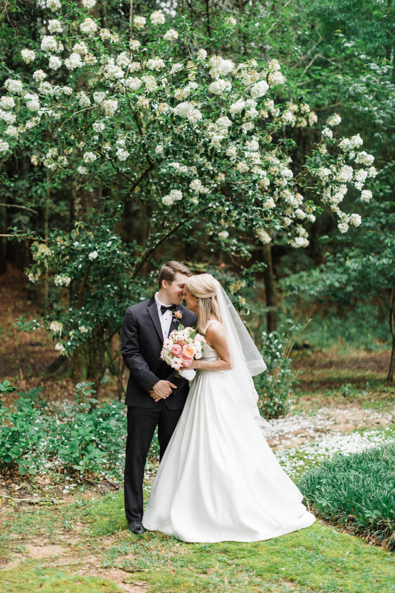 Bride and Groom standing in the family's backyard by flowers