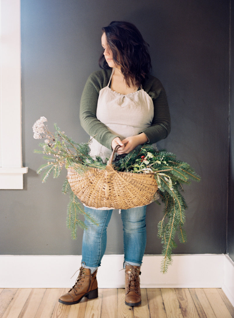 Branding Portrait of Victoria Fiaretti  holding a woven basket of flowers and greenery against a gray wall with soft light | Pittsburgh Branding Photographer | Anna Laero