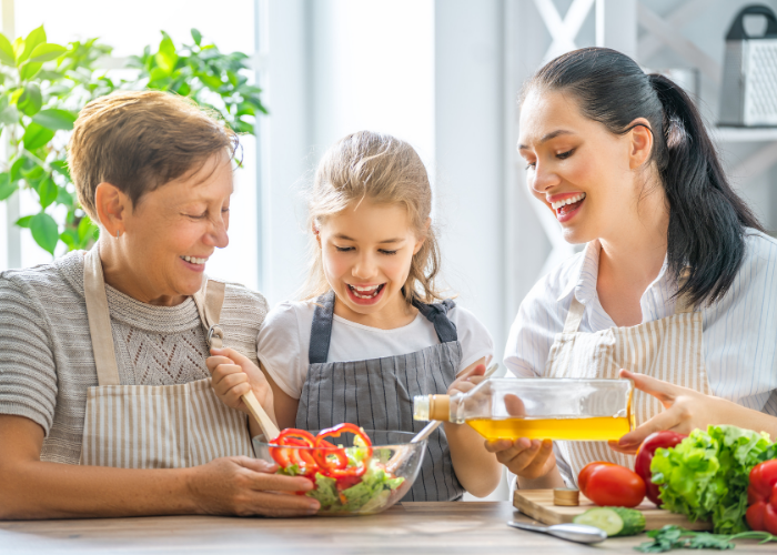 Thrive by Spectrum Pediatrics image for article titled introduction to the Spectrum Pediatrics tube weaning program is a child preparing food for mealtime with her mother and grandmother representing three generations