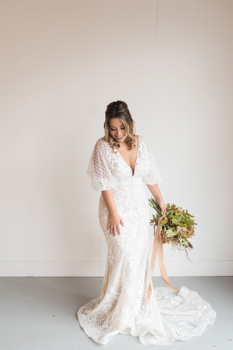 Nashville bride in a beaded dress in front of white wall