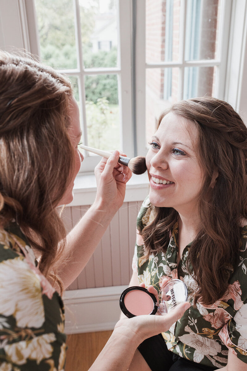Maid of Honour putting make up on Bride
