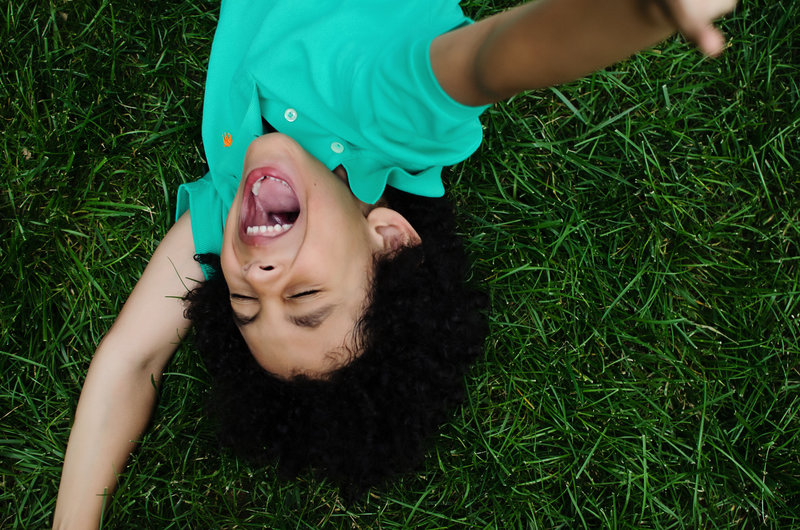 Lifestyle portrait of happy kid playing in grass