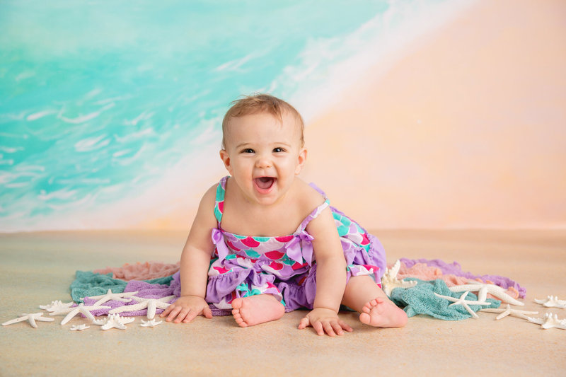 baby girl smiles in front of a beach background