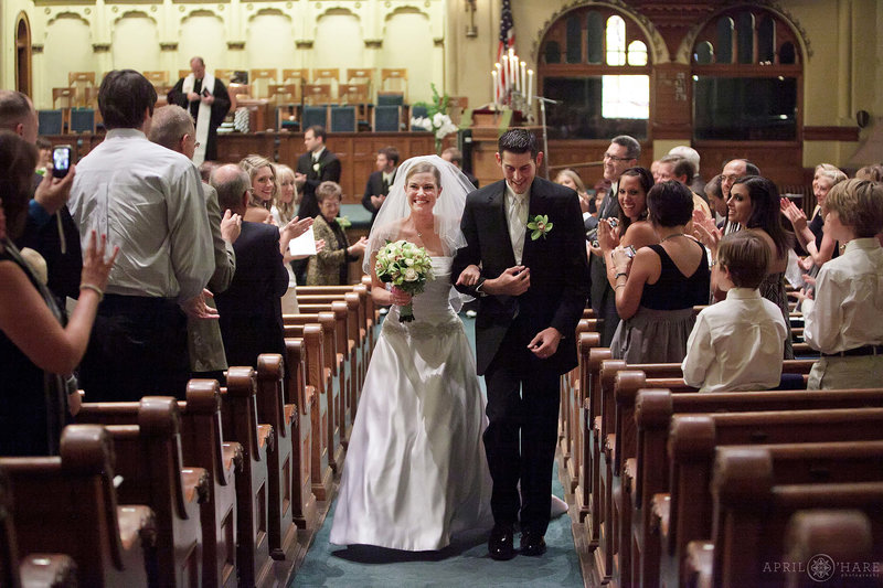 Bride and groom walk down the aisle after ceremony at Central Presbyterian Church in downtown Denver