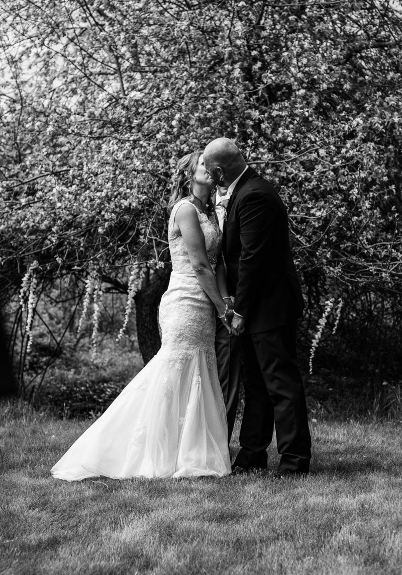 Bride and groom share a kiss under a blooming tree at their Erie, PA outdoor wedding