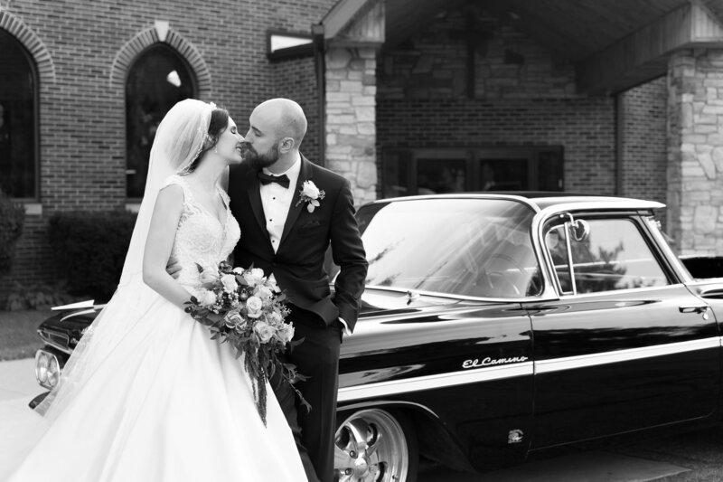 bride and groom in front of vintage car on wedding day