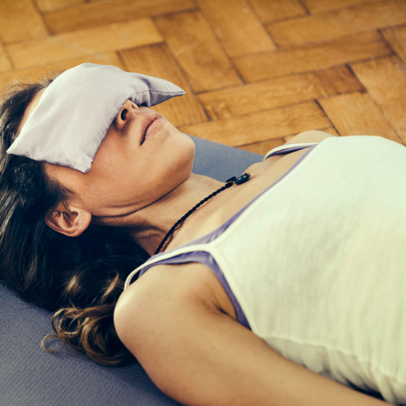 A woman with an eye pillow over her eyes in savasana