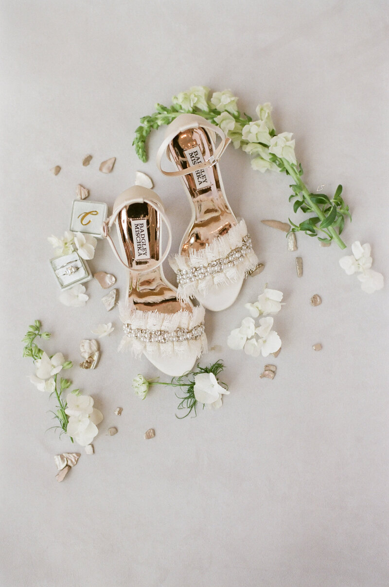 Flat-lay of white fringed high-heels, green stems with white flowers, wedding rings in a decorative box