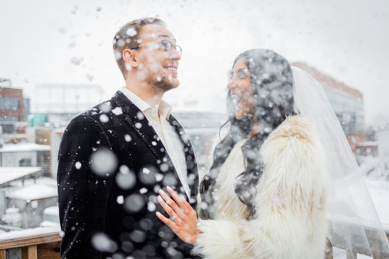 Man and woman laughing while it snows