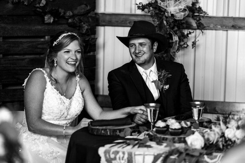 Bride and groom laughing together at head table during wedding reception in Waterford PA