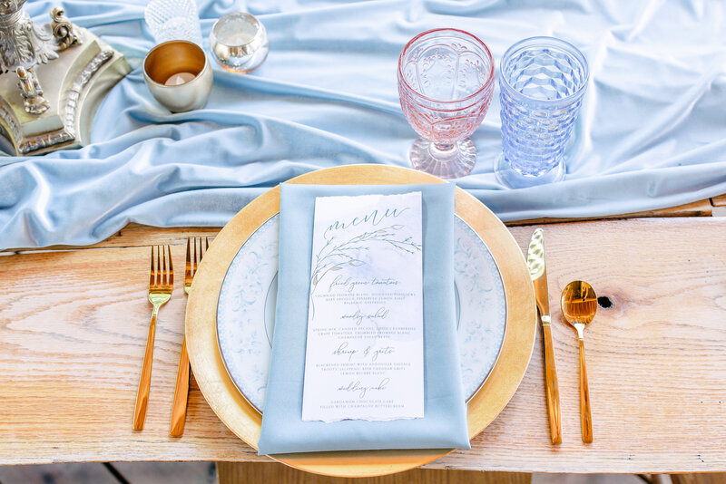 A white menu sits atop a pale blue napkin adorning a gold table setting with a pink goblet.
