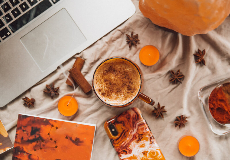 flatlay of a phone, laptop, notebook, anise stars, coffee