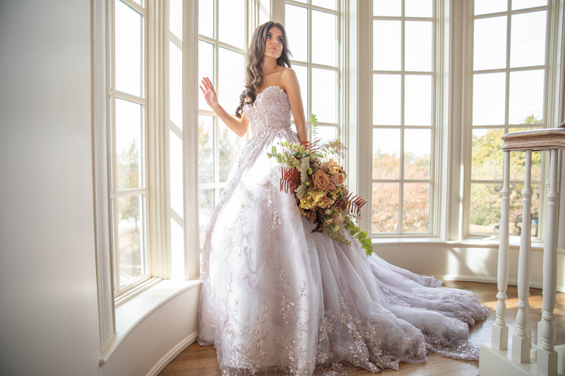 bride holds bouquet near elegant windows