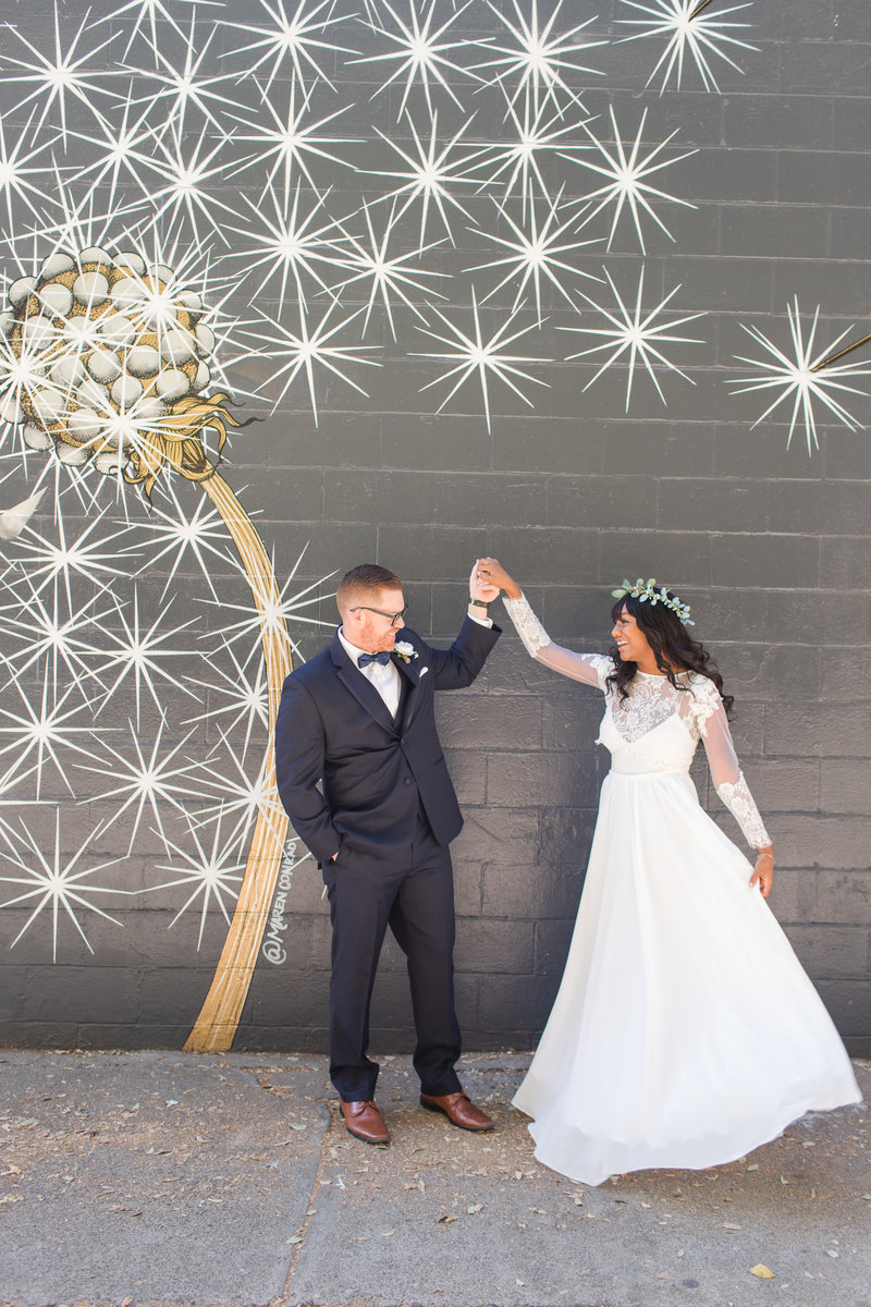 A bride and groom dance in front of a mural at their downtown Sacramento wedding.