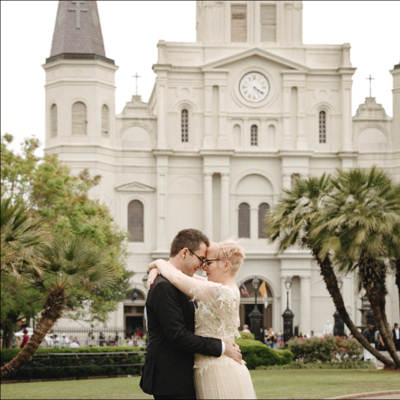Couple embraces on their wedding day in front of St Louis Cathedral in Jackson Square New Orleans