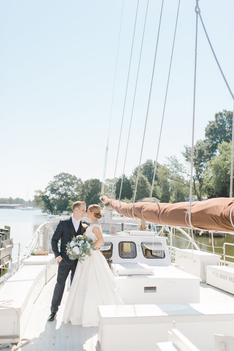 bride and groom kissing on sailboat at Inn at Perry Cabin wedding in St Michaels Maryland by Costola Photography